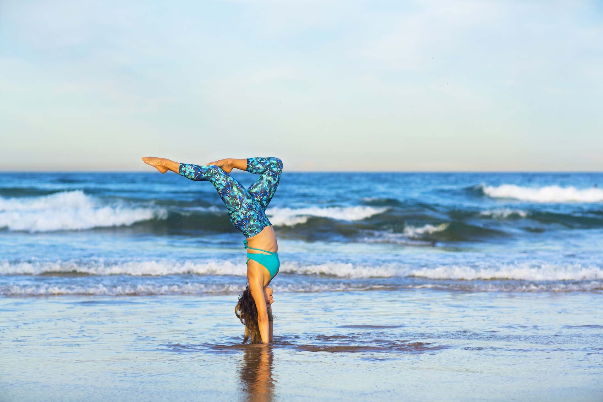 Woman doing a yoga handstand at the beach