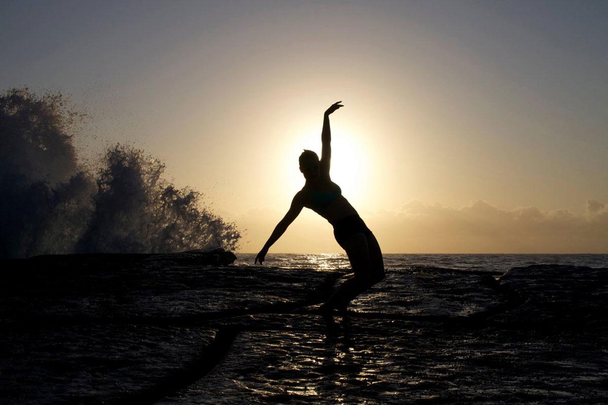 Woman dancing at sunrise at the beach