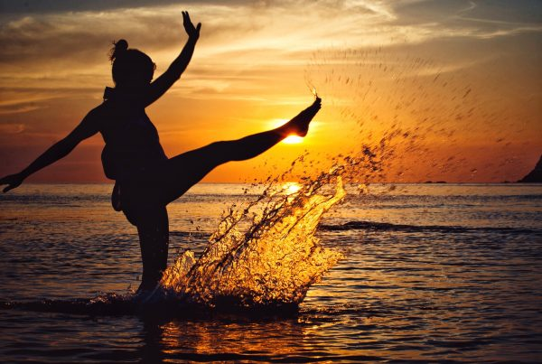 Woman dancing in the sunset at the beach