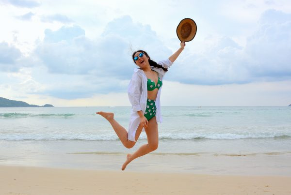 Woman jumping happily on the beach