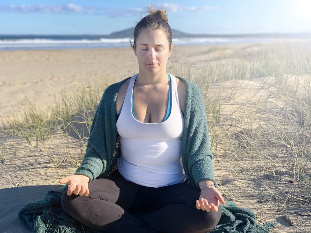 Woman sitting at the beach in meditation