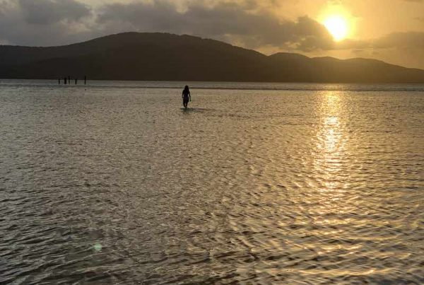 Woman standing in a lake at sunset
