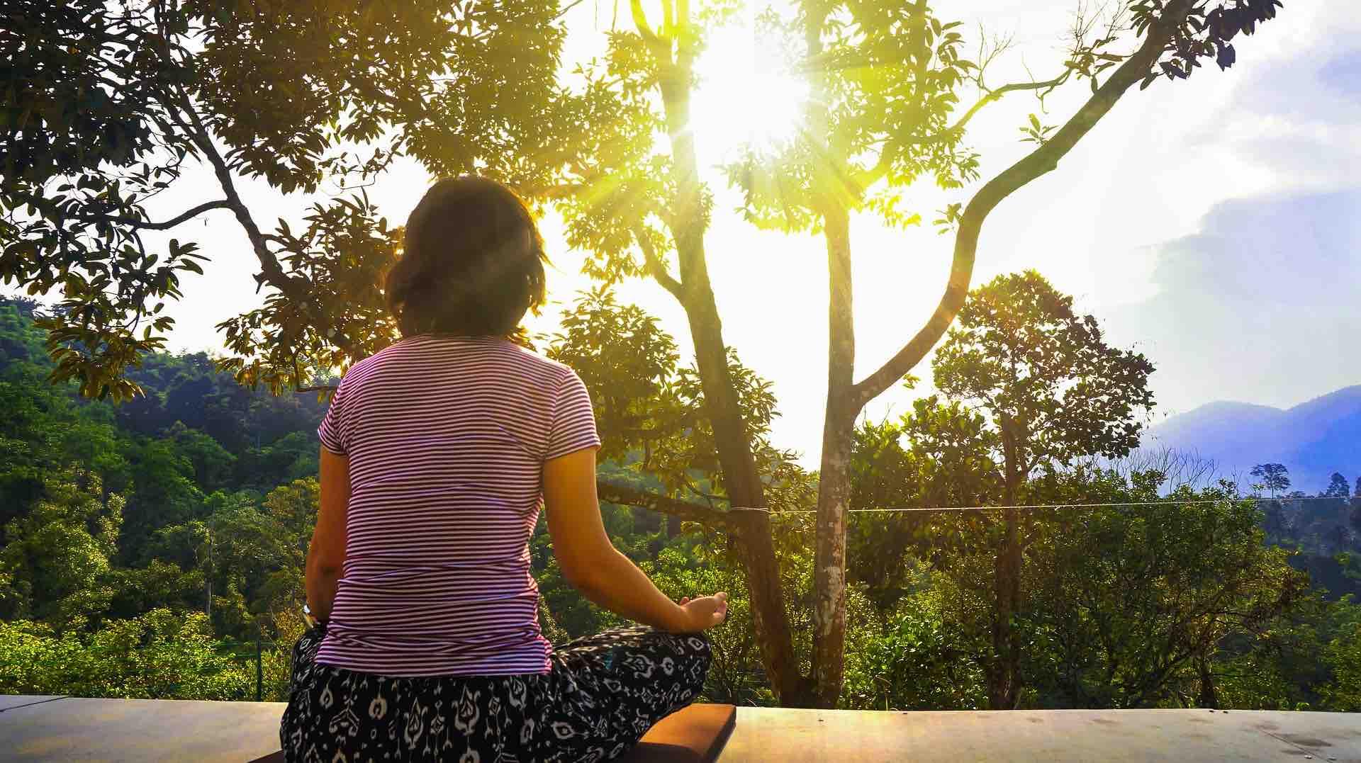 Woman meditating next to trees
